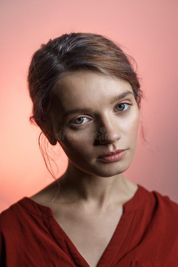 Αρκετά αισθησιακό καυκάσιο κορίτσι στο κόκκινο πουκάμισο που εξετάζει τη κάμερα και που γέρνει το κεφάλι της Πορτρέτο ομορφιάς στ στοκ εικόνες με δικαίωμα ελεύθερης χρήσης