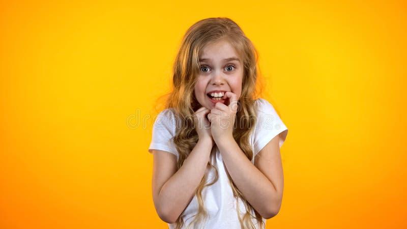 Αρκετά ανήσυχο ξανθό δάχτυλο δαγκώματος κοριτσιών και κοίταγμα στη κάμερα, που υφίσταται το φόβο στοκ φωτογραφία