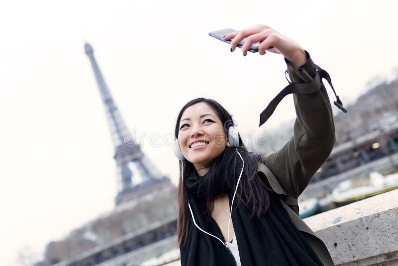 Αρκετά ασιατική νέα γυναίκα που παίρνει ένα selfie μπροστά από τον πύργο του Άιφελ στο Παρίσι ακούοντας τη μουσική στοκ φωτογραφίες
