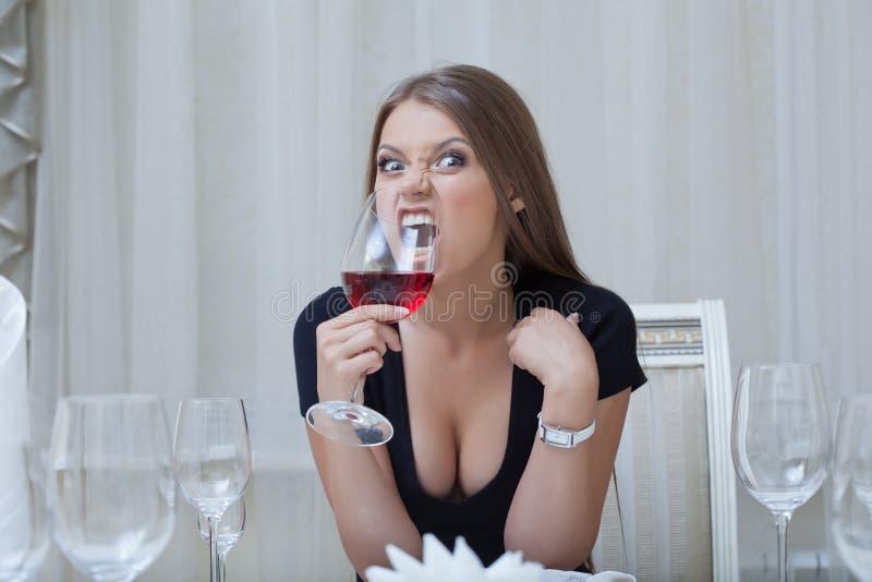 Αρκετά αστείο ποτήρι δαγκώματος κοριτσιών του κρασιού, κινηματογράφηση σε πρώτο πλάνο στοκ εικόνα