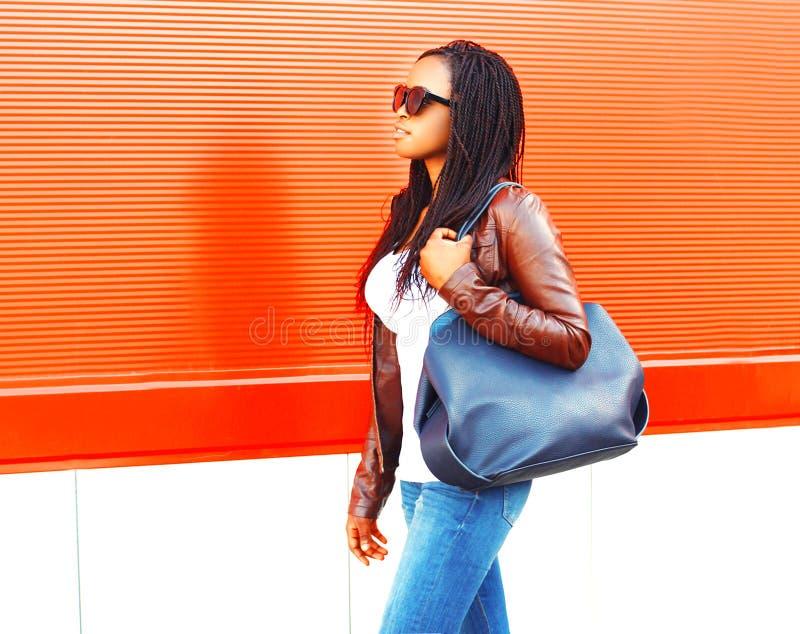 Αρκετά αφρικανική γυναίκα με την τσάντα που περπατά στην πόλη πέρα από το κόκκινο στοκ φωτογραφία με δικαίωμα ελεύθερης χρήσης