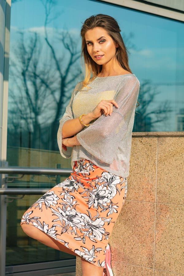 Αρκετά ελκυστική και νέα τοποθέτηση γυναικών στην οδό στα ζωηρόχρωμα ενδύματα στοκ εικόνες