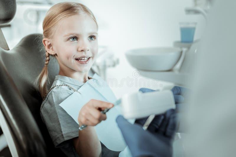 Αρκετά ενδιαφερόμενη φέρνοντας οδοντόβουρτσα κοριτσιών καθμένος στοκ φωτογραφία