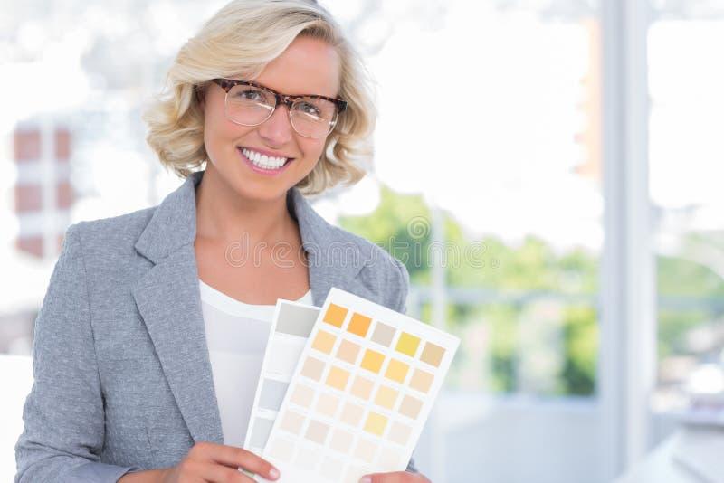 Αρκετά εσωτερικός σχεδιαστής που κρατά ψηλά τα δείγματα χρώματος στοκ εικόνες