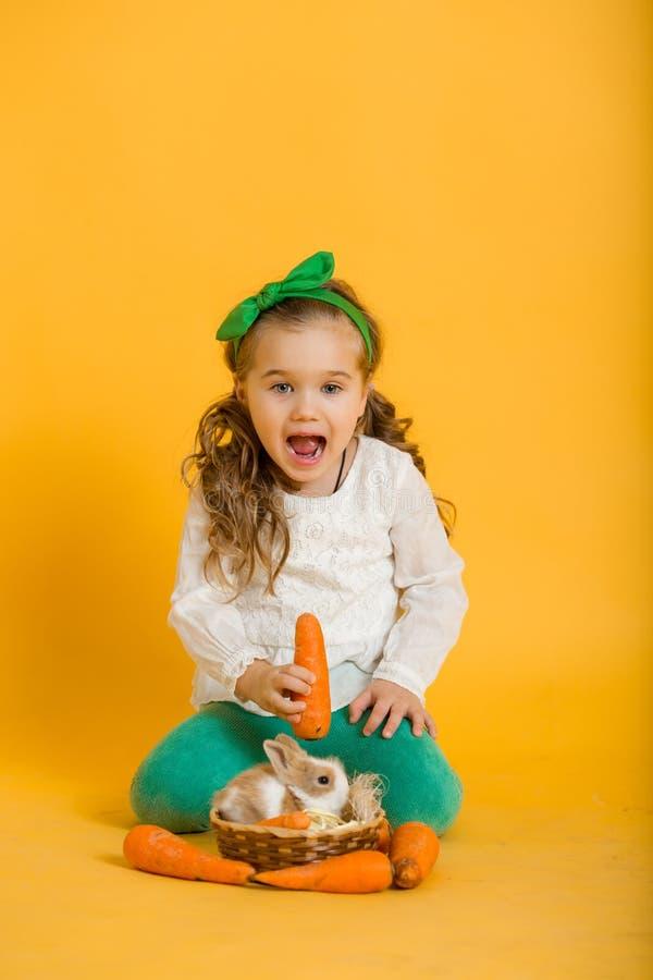 Αρκετά ευτυχές κορίτσι παιδιών με τα καρότα και ο φίλος της λίγο ζωηρόχρωμο κουνέλι, έννοια διακοπών Πάσχας στοκ εικόνα