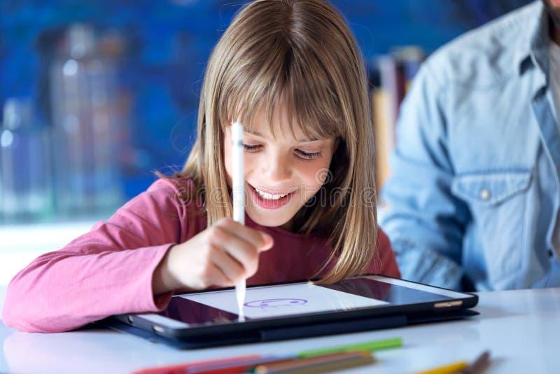 Αρκετά ευτυχές σχέδιο μικρών κοριτσιών με την ψηφιακή ταμπλέτα στο σπίτι στοκ εικόνα με δικαίωμα ελεύθερης χρήσης