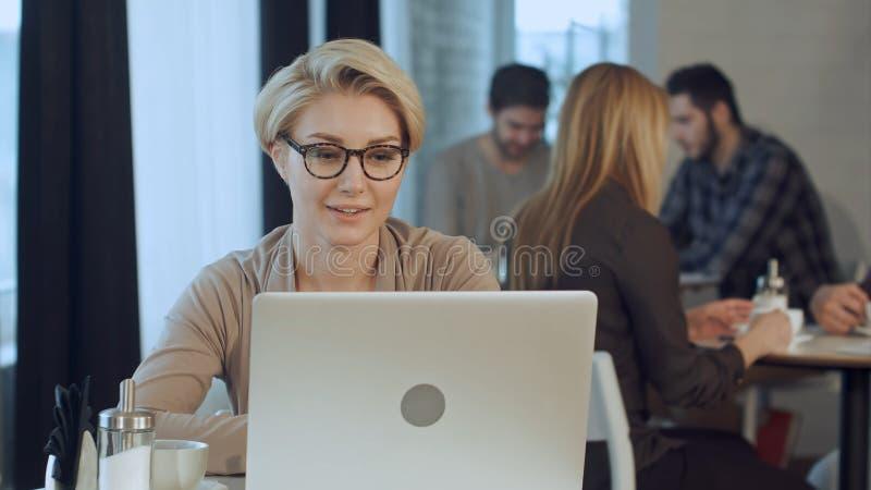 Αρκετά ευτυχής γυναίκα που εργάζεται στο φορητό προσωπικό υπολογιστή κατά τη διάρκεια του διαλείμματος στο φραγμό καφέδων στοκ εικόνα