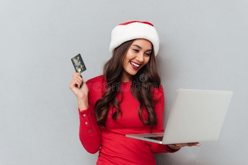 Αρκετά εύθυμη γυναίκα brunette στο πιστωτικό αυτοκίνητο εκμετάλλευσης καπέλων Santa ` s στοκ φωτογραφίες