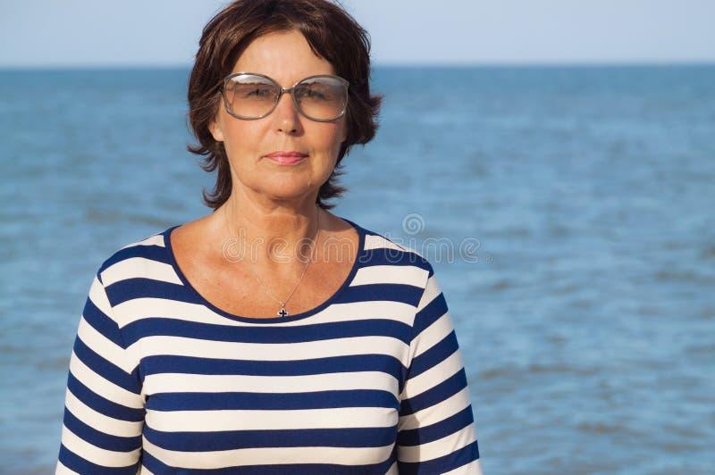 Αρκετά ηλικιωμένη γυναίκα στις διακοπές στην παραλία στοκ φωτογραφία
