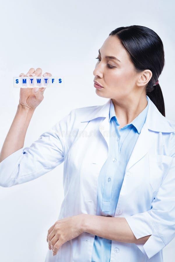 Αρκετά θηλυκός γιατρός που εξετάζει το διοργανωτή χαπιών στα χέρια της στοκ εικόνες