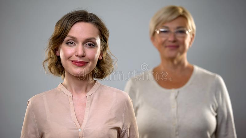Αρκετά θηλυκό χαμόγελο στη κάμερα, ηλικιωμένη κυρία πίσω, εξασφαλισμένη και υγιής γήρανση στοκ φωτογραφία