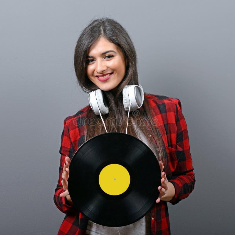 Αρκετά θηλυκό DJ με τα ακουστικά και βινύλιο στο γκρίζο κλίμα στοκ εικόνες