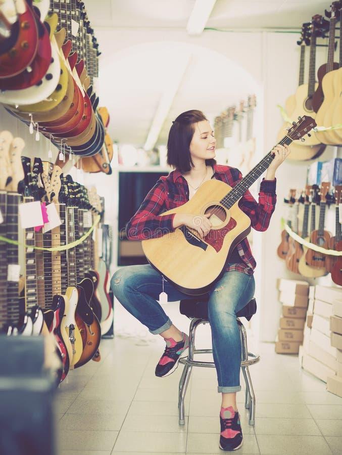 Αρκετά θηλυκός έφηβος που εξετάζει τις διάφορες ακουστικές κιθάρες στοκ φωτογραφίες