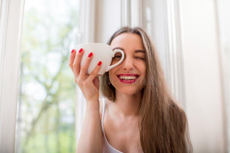 Αρκετά και συνεδρίαση κοριτσιών χαμόγελου κοντά στο παράθυρο και εξέταση το τ στοκ φωτογραφία με δικαίωμα ελεύθερης χρήσης