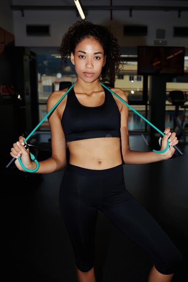 Αρκετά κατάλληλο κορίτσι με τη σγουρή τρίχα που έχει ένα υπόλοιπο μετά από το workout στοκ εικόνες