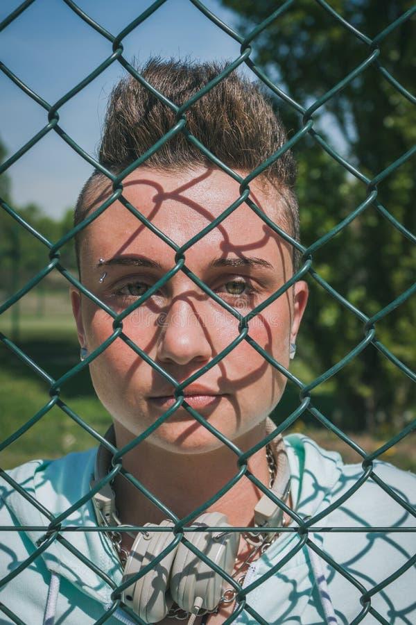 Αρκετά κοντό κορίτσι τρίχας πίσω από ένα μεταλλικό δίχτυ στοκ φωτογραφία με δικαίωμα ελεύθερης χρήσης