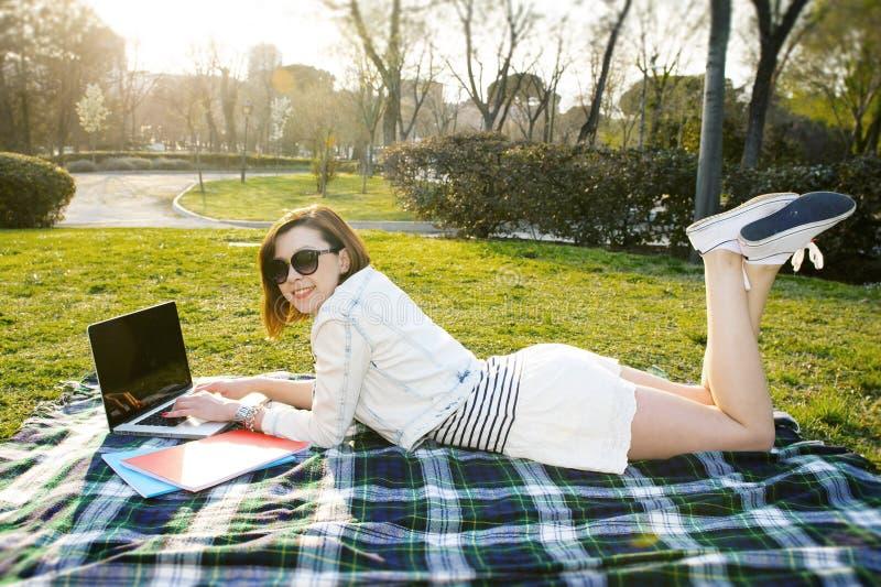 Αρκετά κόκκινη γυναίκα τρίχας που εργάζεται στο lap-top στο πάρκο στοκ εικόνα με δικαίωμα ελεύθερης χρήσης