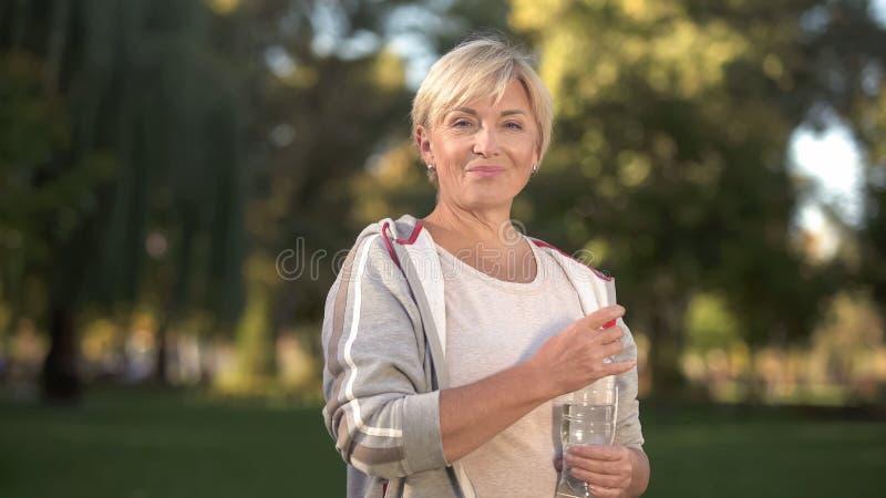 Αρκετά μέσο ηλικίας πόσιμο νερό γυναικών στο πάρκο, που κρατά την ισορροπία νερού, υγεία στοκ φωτογραφίες