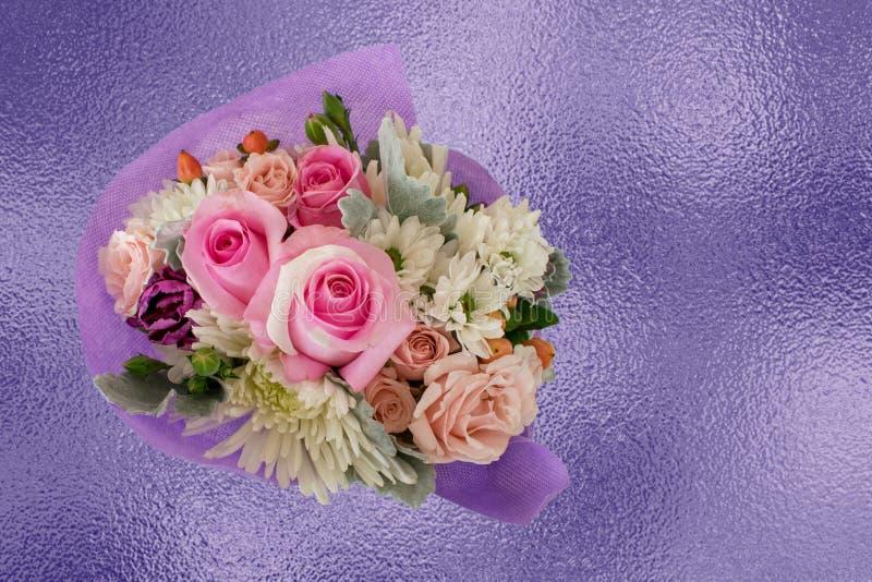 Αρκετά μικροσκοπική ανθοδέσμη με τα ρόδινα τριαντάφυλλα στο πορφυρό backgrou φύλλων αλουμινίου στοκ εικόνα