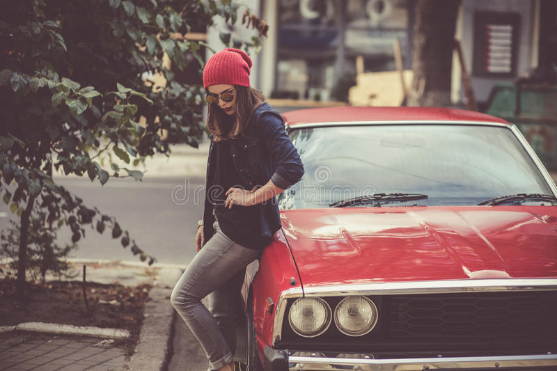 Αρκετά μοντέρνη γυναίκα που υπερασπίζεται το αναδρομικό αυτοκίνητο στοκ εικόνες