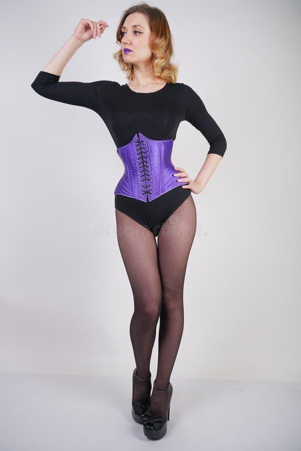 Αρκετά μοντέρνο ξανθό κορίτσι που φορά το μαύρο jumpsuit με το πλέγμα pantyhose και τον πορφυρό κορσέ στο άσπρο υπόβαθρο στοκ εικόνα με δικαίωμα ελεύθερης χρήσης