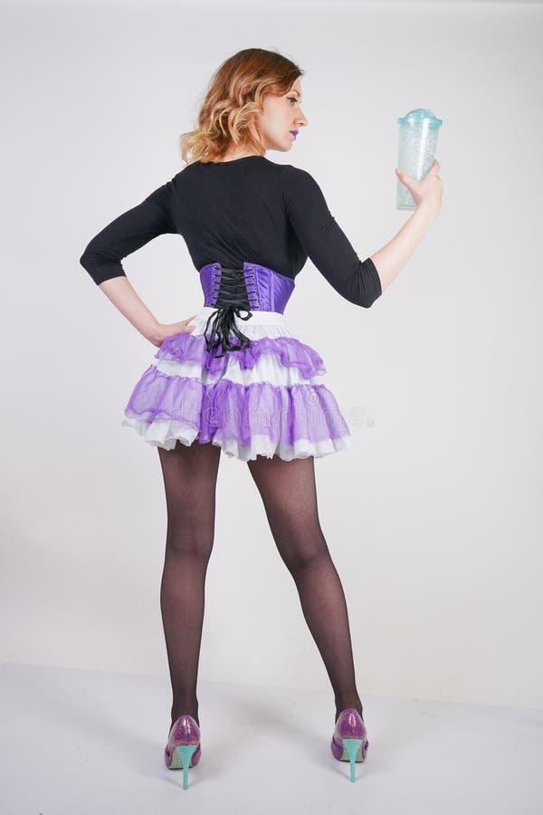 Αρκετά μοντέρνο ξανθό κορίτσι που φορά το μαύρο jumpsuit με το πλέγμα pantyhose και τον πορφυρό κορσέ στο άσπρο υπόβαθρο στοκ εικόνες