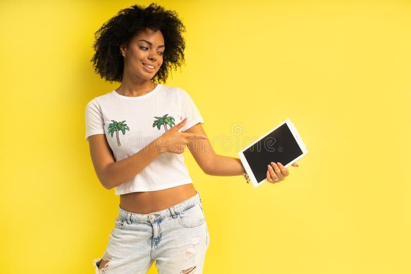 Αρκετά νέα αμερικανική γυναίκα afro που στέκεται και που χρησιμοποιεί τον υπολογιστή ταμπλετών που απομονώνεται πέρα από το κίτρι στοκ εικόνα με δικαίωμα ελεύθερης χρήσης