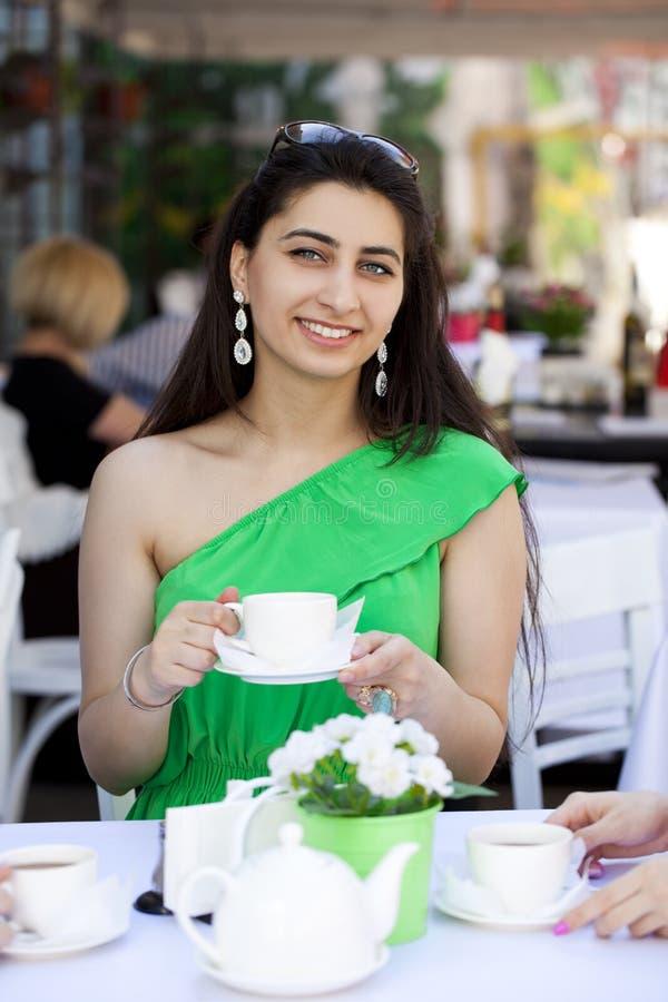 Αρκετά νέα αραβική συνεδρίαση γυναικών στον καφέ στοκ φωτογραφία