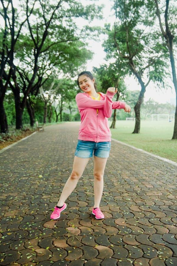 Αρκετά νέα ασιατικά excercises στο πάρκο το πρωί Φρέσκος και υγιής τρόπος ζωής για τους ανθρώπους στοκ φωτογραφία