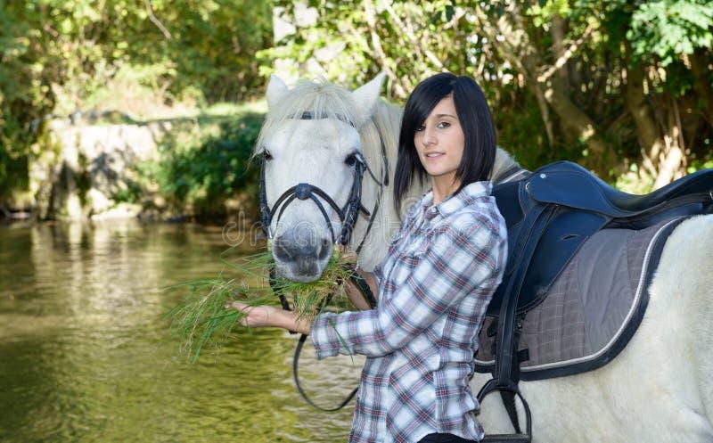 Αρκετά νέα γυναίκα με την άσπρη ιππασία στον ποταμό στοκ φωτογραφίες με δικαίωμα ελεύθερης χρήσης