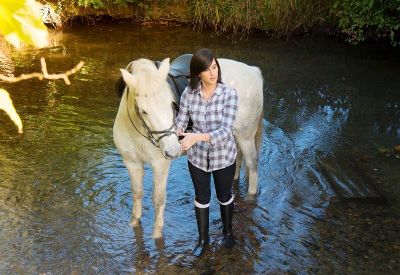 Αρκετά νέα γυναίκα με την άσπρη ιππασία στον ποταμό στοκ εικόνες