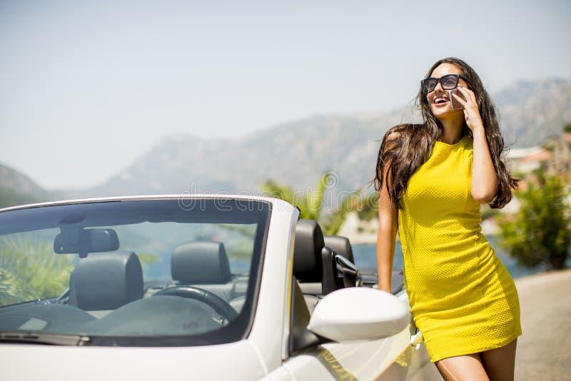 Αρκετά νέα γυναίκα με το κινητό τηλέφωνο με το άσπρο αυτοκίνητο καμπριολέ στοκ φωτογραφίες