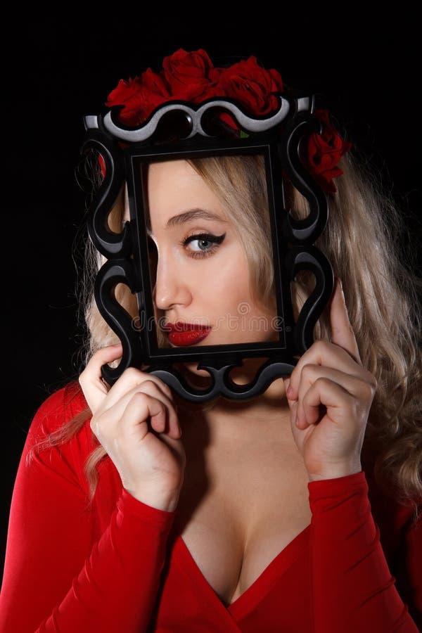 Αρκετά νέα γυναίκα που κρατά ένα πλαίσιο μπροστά από το πρόσωπό της στοκ εικόνα με δικαίωμα ελεύθερης χρήσης