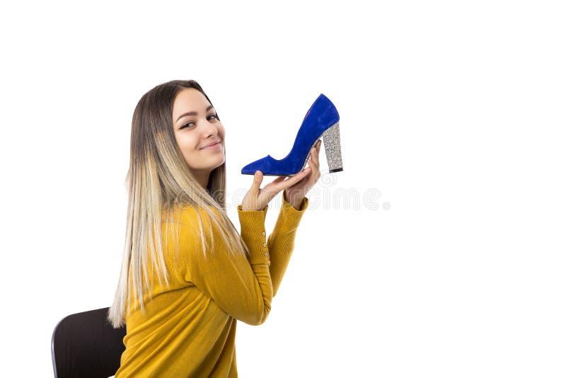 Αρκετά νέα γυναίκα που κρατά ένα υψηλό παπούτσι τακουνιών πέρα από το άσπρο υπόβαθρο στοκ φωτογραφία