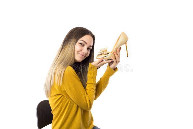 Αρκετά νέα γυναίκα που κρατά ένα υψηλό παπούτσι τακουνιών πέρα από το άσπρο υπόβαθρο στοκ φωτογραφίες με δικαίωμα ελεύθερης χρήσης