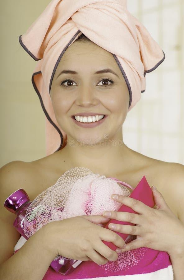 Αρκετά νέα γυναίκα που τυλίγεται με τις πετσέτες λουτρών που κρατούν το σαμπουάν και loofah το σφουγγάρι στοκ φωτογραφίες
