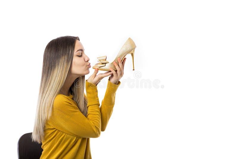 Αρκετά νέα γυναίκα που φιλά ένα υψηλό παπούτσι τακουνιών πέρα από το άσπρο υπόβαθρο στοκ φωτογραφία