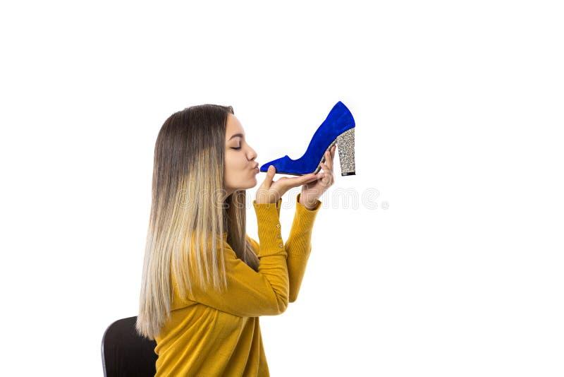 Αρκετά νέα γυναίκα που φιλά ένα υψηλό παπούτσι τακουνιών πέρα από το άσπρο υπόβαθρο στοκ εικόνες