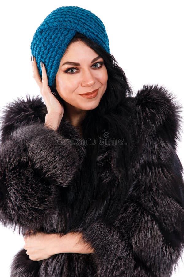 Αρκετά νέα γυναίκα σε ένα μαύρα παλτό και ένα τουρμπάνι γουνών στοκ εικόνες