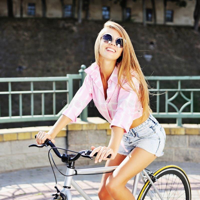 Αρκετά νέα γυναίκα σε ένα υπαίθριο πορτρέτο μόδας ποδηλάτων στοκ φωτογραφίες
