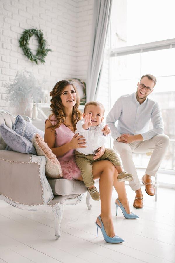 Αρκετά νέα οικογένεια που έχει τη διασκέδαση διακοσμημένο στο φως στούντιο στοκ φωτογραφία