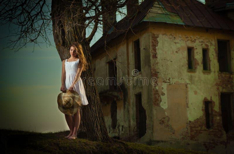 Αρκετά νέα τοποθέτηση γυναικών μπροστά από το αγρόκτημα. Πολύ ελκυστικό ξανθό κορίτσι με το άσπρο κοντό φόρεμα που κρατά ένα καπέλ στοκ φωτογραφία με δικαίωμα ελεύθερης χρήσης