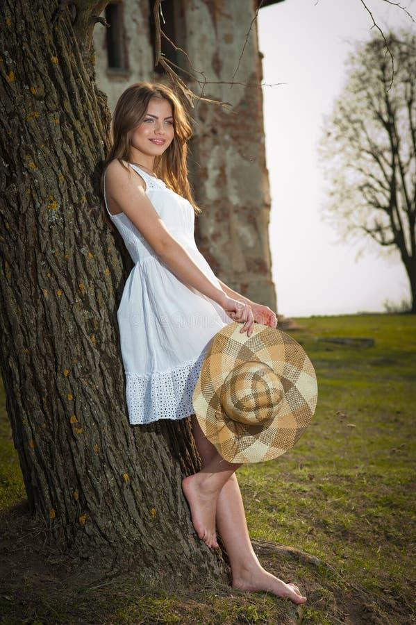 Αρκετά νέα τοποθέτηση γυναικών μπροστά από το αγρόκτημα. Πολύ ελκυστικό ξανθό κορίτσι με το άσπρο κοντό φόρεμα που κρατά ένα καπέλ στοκ εικόνα