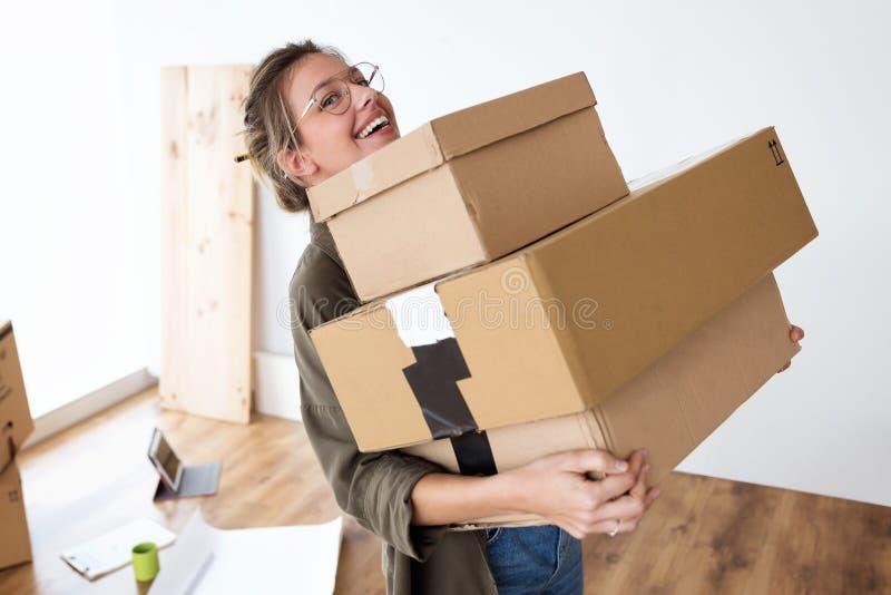Αρκετά νέα φέρνοντας κουτιά από χαρτόνι γυναικών στο καινούργιο σπίτι της χαμογελώντας στη κάμερα στοκ φωτογραφία