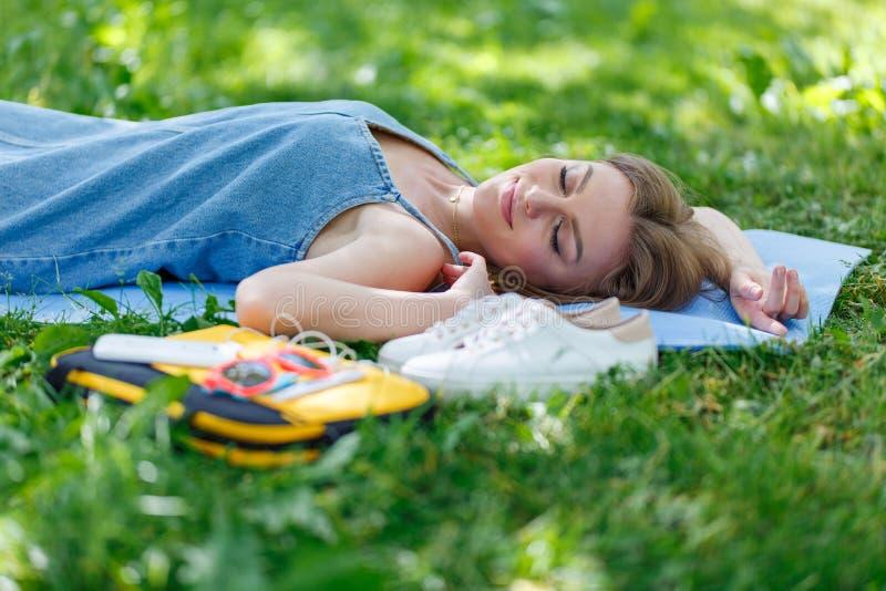 Αρκετά νέα χαλάρωση γυναικών στη χλόη σε ένα πάρκο Τοπ όψη στοκ φωτογραφία με δικαίωμα ελεύθερης χρήσης