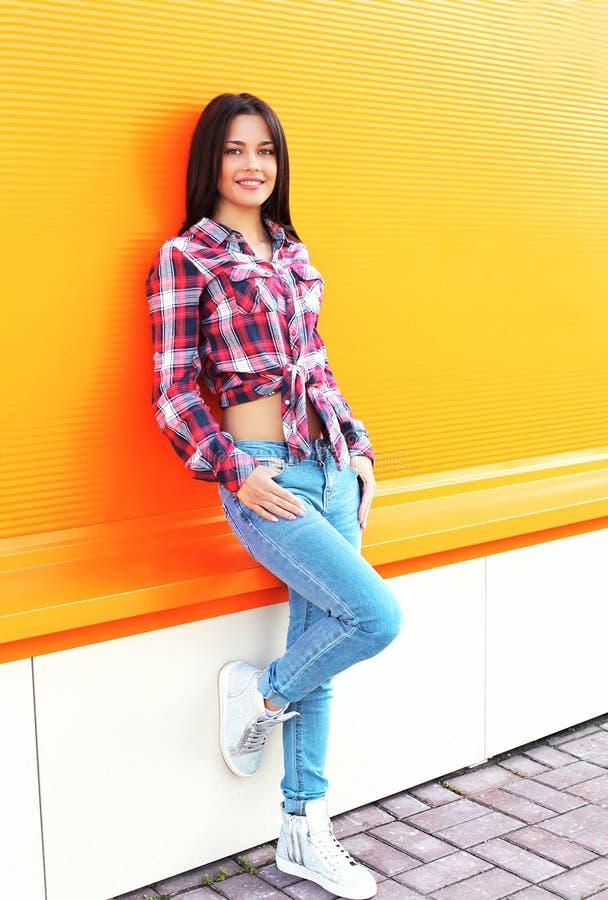 Αρκετά νέα χαμογελώντας γυναίκα που φορά ένα ελεγμένο πουκάμισο και τα τζιν στοκ εικόνες