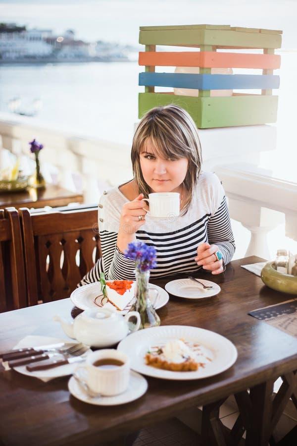 Αρκετά νέος τσάι ή καφές κατανάλωσης γυναικών σε έναν καφέ στοκ φωτογραφίες με δικαίωμα ελεύθερης χρήσης