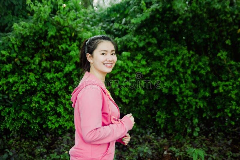 Αρκετά νέο ασιατικό κορίτσι που τρέχει στο πάρκο το πρωί Φρέσκος και υγιής τρόπος ζωής για τους ανθρώπους στοκ εικόνες με δικαίωμα ελεύθερης χρήσης