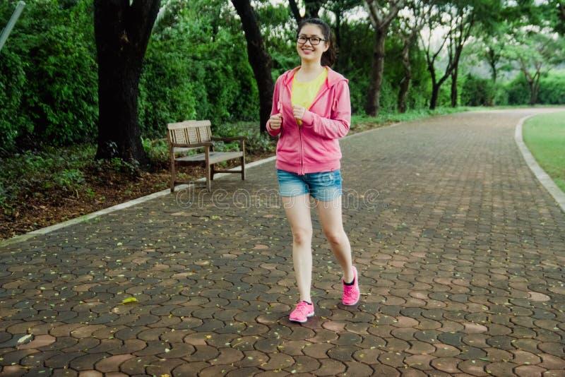 Αρκετά νέο ασιατικό κορίτσι που τρέχει στο πάρκο το πρωί Φρέσκος και υγιής τρόπος ζωής για τους ανθρώπους στοκ φωτογραφία με δικαίωμα ελεύθερης χρήσης