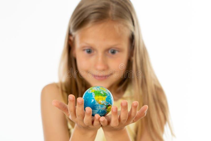 Αρκετά νέο ξανθό κορίτσι στην κίτρινη μπλούζα που εξετάζει τη μικρή σφαίρα ι στοκ φωτογραφία με δικαίωμα ελεύθερης χρήσης